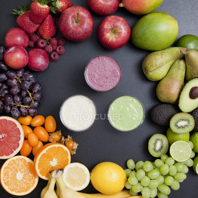 Still life of variety of fruit surrounding fresh smoothies — Stock Photo