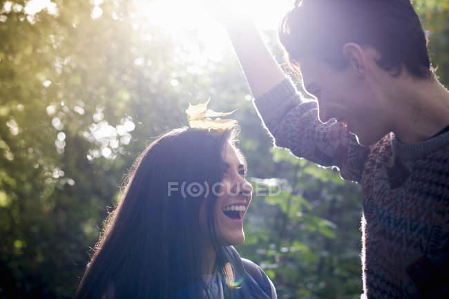 Giovane coppia che gioca con foglie autunnali nella foresta — Foto stock