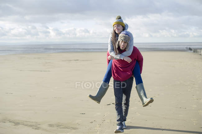 Hombre devolviendo cerdito a mujer, Brean Sands, Somerset, Inglaterra - foto de stock
