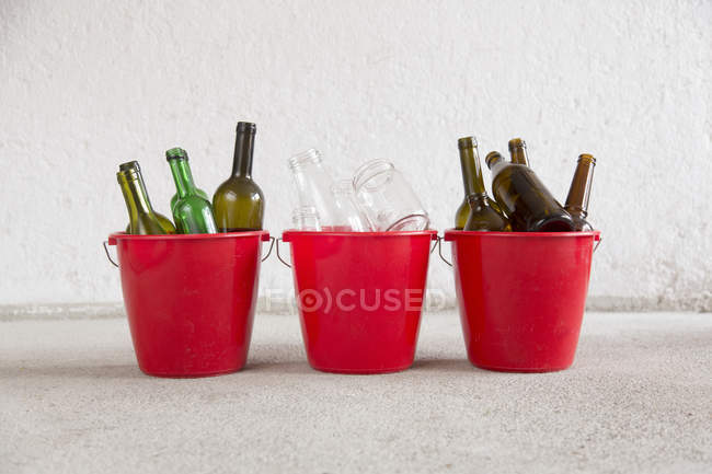 Three recycling buckets in garage with green, brown and transparent bottles — Stock Photo