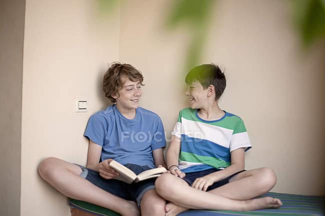 Підліткові хлопчики сидять на ліжку з книгою — стокове фото