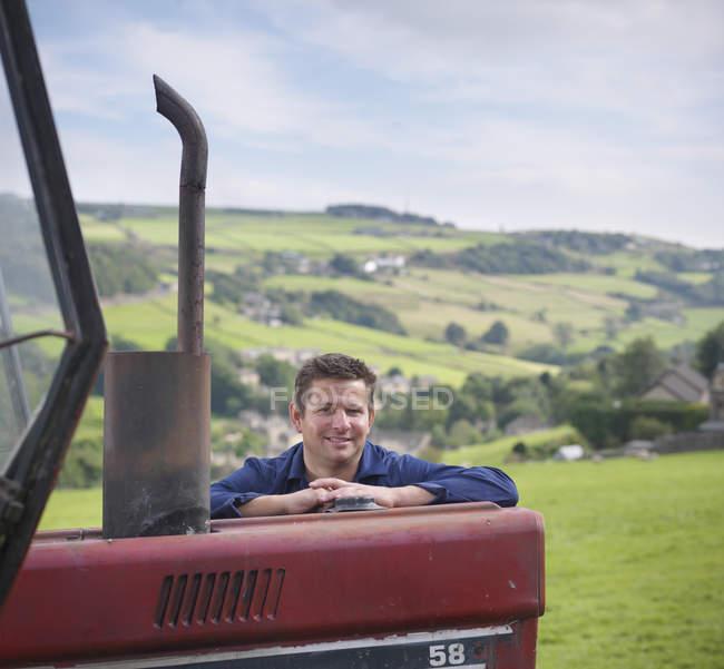 Portrait d'agriculteur appuyé sur un tracteur dans un champ, souriant — Photo de stock
