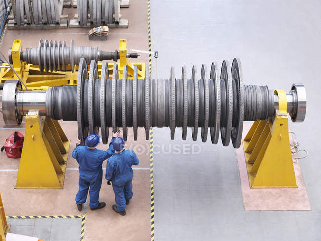 Engineers inspecting turbine during power station outage, high angle view — Stock Photo