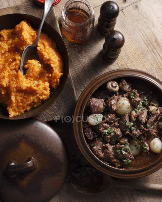 Tazones de fuente de puré dulce de papas y carne de vaca bourguignon en mesa - foto de stock