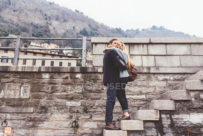 Молодая пара, обнимающая стены гавани ступенек, озеро Комо, Италия — стоковое фото
