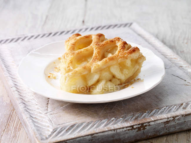 Brambly apple pie slice on wooden chopping board — Stock Photo