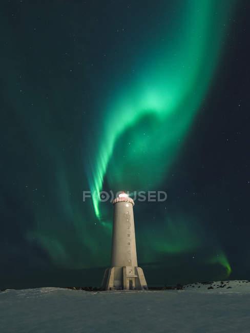 Aurora Boreal remolino verde sobre Faro de noche - foto de stock