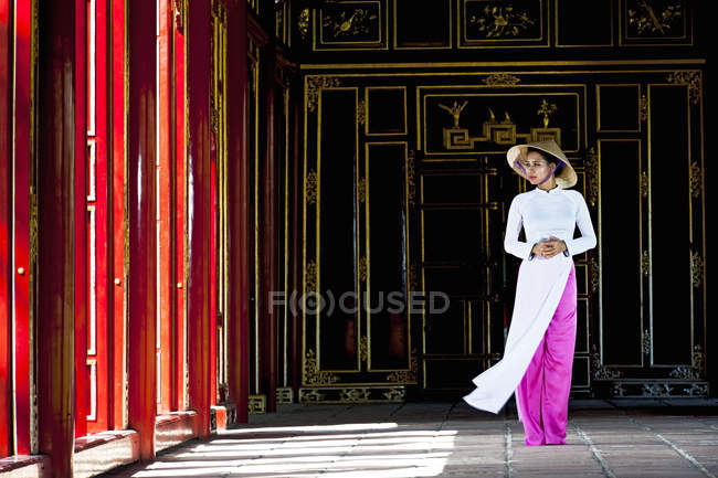 Mid adult woman wearing ao dai dress and conical hat standing in imperial palace looking away, Hue, Vietnam — Stock Photo