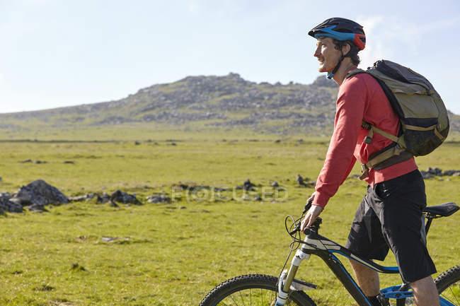 Vista lateral del ciclista ciclismo en ladera - foto de stock