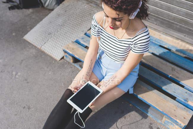 Donna seduta su pallet con le cuffie in possesso di tablet digitale — Foto stock