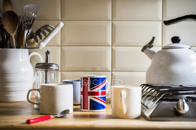 Кухонного столу з Глечик з посудом і гуртки кави — стокове фото