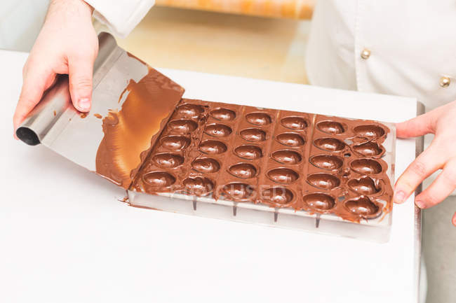 Cropped image of Chef scraping chocolate in kitchen — Stock Photo