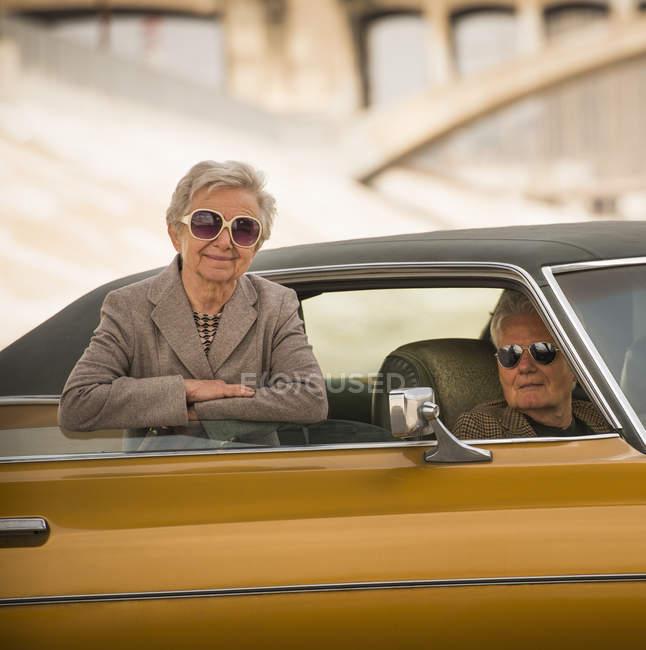 Verticale de couple aîné frais avec l'automobile classique — Photo de stock