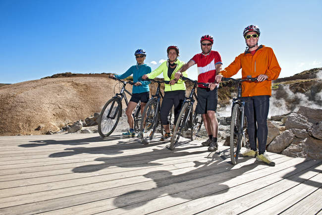 Portrait of four cyclists with hybrid bikes at geothermal site, Krysuvik, Reykjanes, Iceland - foto de stock