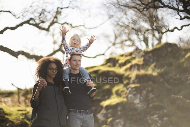 Familia a pie, padre llevando a su hijo en hombros - foto de stock