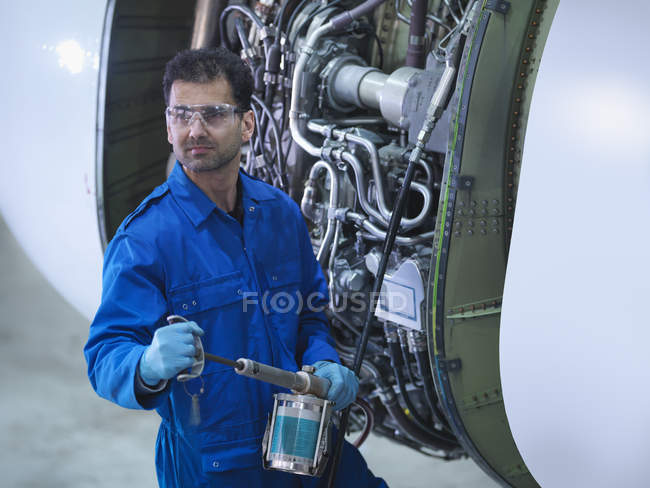 Инженеры, работающие над реактивным двигателем на авиаремонтном заводе, портрет — стоковое фото