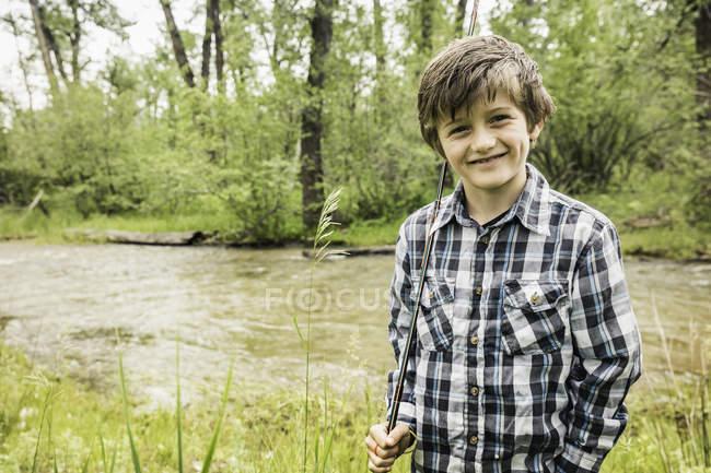 Niño con camisa a cuadros con caña por río mirando a la cámara sonriendo - foto de stock