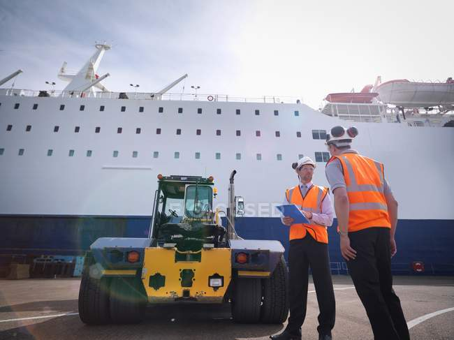 Port workers and shipping container truck and ship in port — Stock Photo