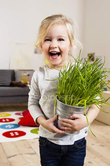Girl carrying potted plant — Stock Photo