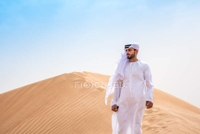 Middle eastern man wearing traditional clothes on desert dune, Dubai, United Arab Emirates — Stock Photo