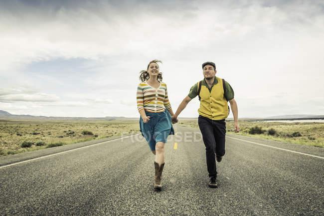 Retro style couple running hand in hand on road, Cody, Wyoming, USA — Stock Photo