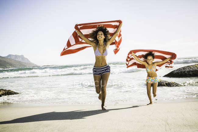 Mère et fille courent sur la plage en tenant une serviette au-dessus de la tête — Photo de stock