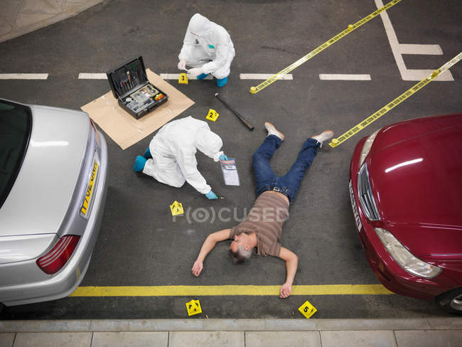 Forensic scientists at crime scene in training facility with person acting as body on floor — Stock Photo