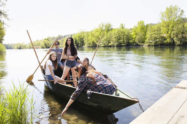 Невелика група молодих дорослих друзів у Веслувати човен на воді — стокове фото