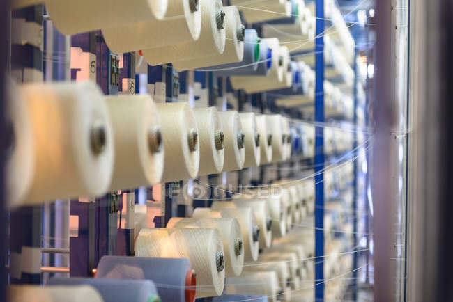 Rows of bobbins of thread in textile mill — Stock Photo