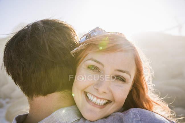Вид через плечо женщины обнимать человек, глядя на камеру улыбается — стоковое фото