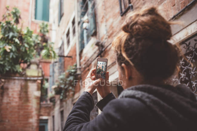 Over the shoulder view of woman photographing buildings on smartphone, Venice, Italy — Stock Photo