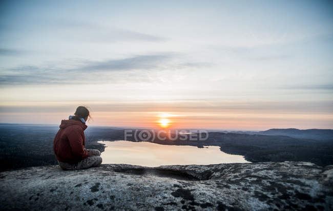 Young female hiker gazing at sunset over distant lake — Stock Photo
