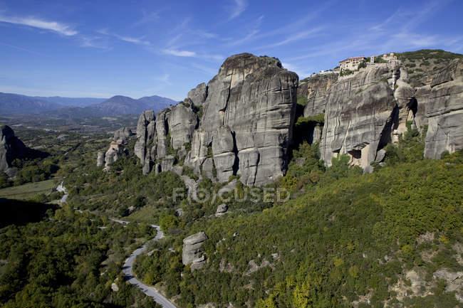 Vallée et monastère construit au sommet de la formation rocheuse — Photo de stock