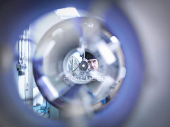 Soffiatore di vetro industriale guardando attraverso tornio di vetro formando — Foto stock
