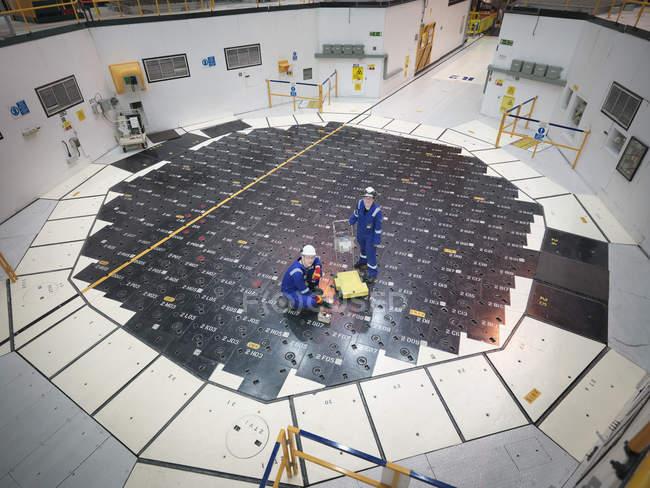 Ingegneri che utilizzano sensori sul tappo di pila nella centrale nucleare, vista ad alto angolo — Foto stock