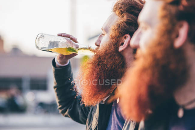 Profile of young male hipster twins with red hair and beards drinking bottled beer — Stock Photo