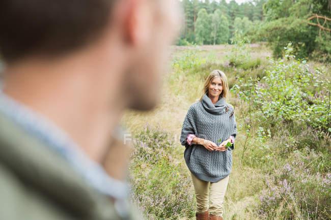 Средний взрослый женщина, держащая листьев, человек, размыты в переднем плане — стоковое фото