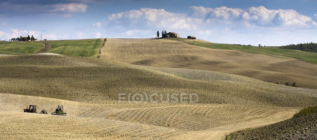 Harvesting machines working in agricultural landscape — Stock Photo