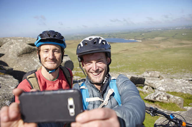 Cyclists with on rocky outcrop taking selfie — Stock Photo