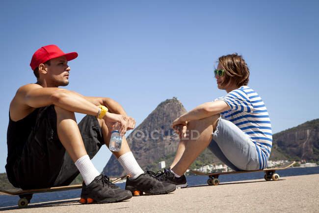 Двое мужчин сидя на скейтбордах, расслабляющий — стоковое фото