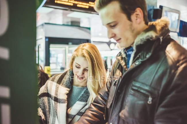 Jeune couple achetant des billets de train à la billetterie — Photo de stock