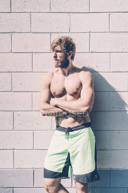 Joven entrenador cruzado masculino con el pecho desnudo apoyado contra la pared fuera del gimnasio - foto de stock