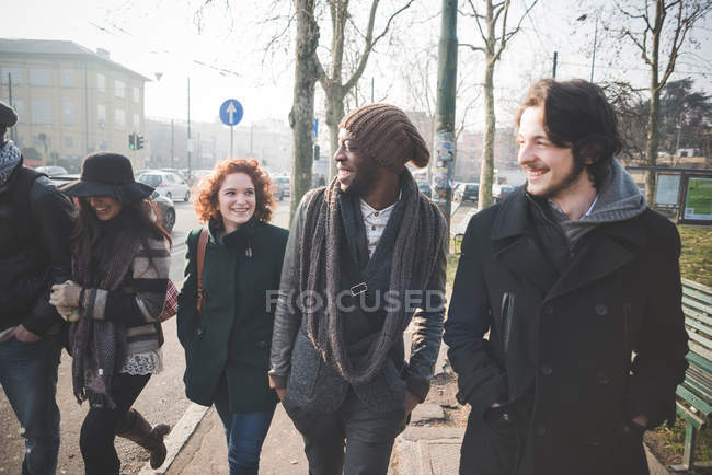 Five young adult friends strolling in city street — Stock Photo