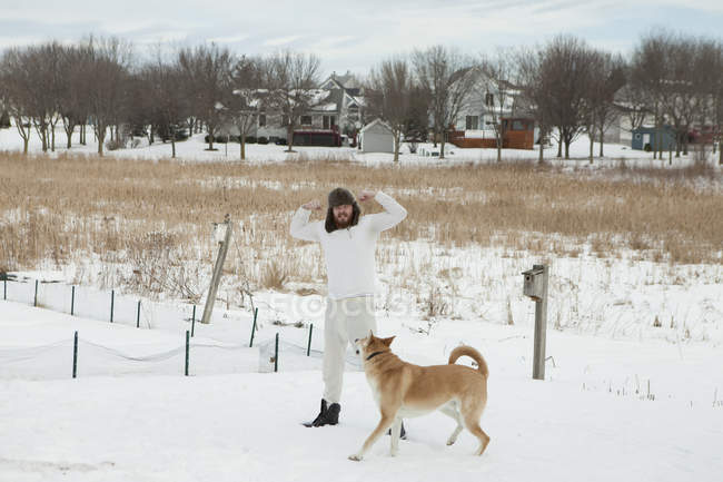 Young man in underwear and fur hat playing with dog in snow — Stock Photo