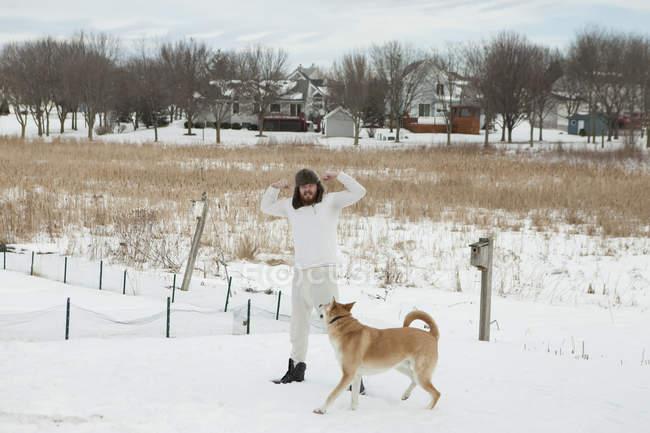 Jovem em roupa interior e chapéu de pele brincando com o cão na neve — Fotografia de Stock