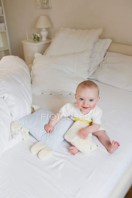 Bebê sorridente, sentada na cama — Fotografia de Stock