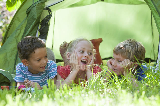 Three children lying chatting in garden tent — Stock Photo