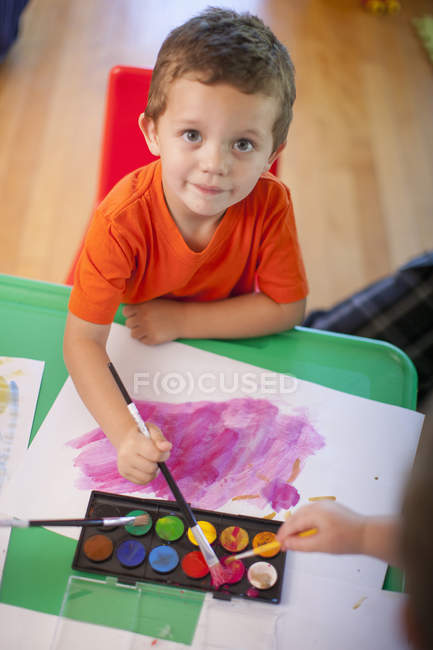 Portrait of boy painting at nursery school — Stock Photo