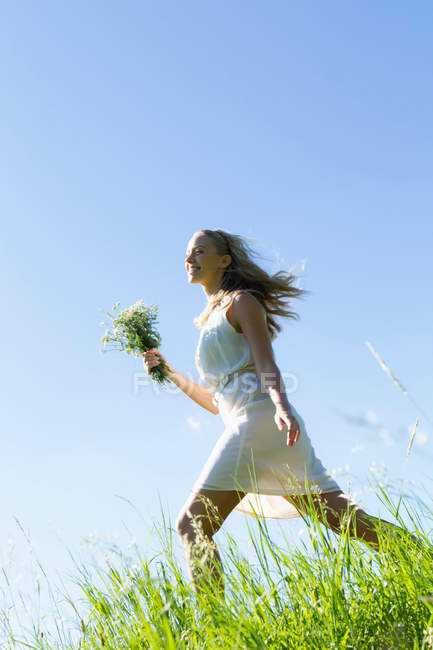 Woman carrying bouquet in tall grass — Stock Photo
