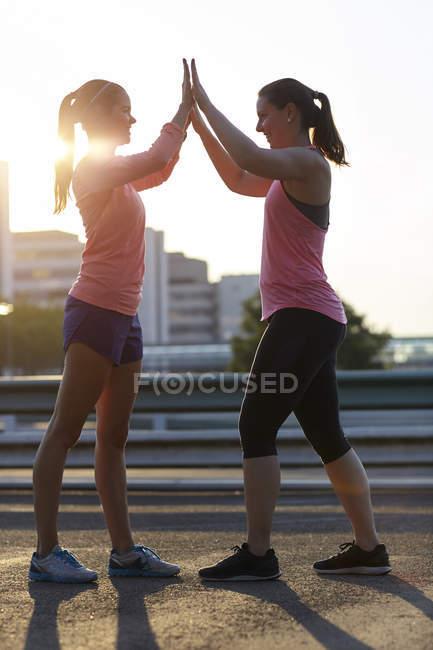 Zwei junge Frauen geben einander hoch fünf auf Dach — Stockfoto